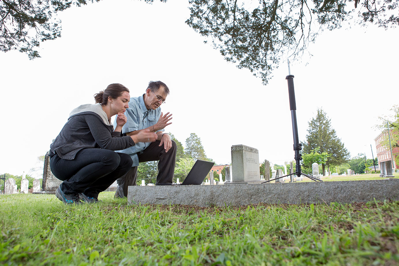Emily Pelland, left, and Dr. Joel Beeson use the Ricoh Theta camera to create a spherical image of Marion Cemetery in Marion, Al. They are trying to match a frame used in a story that other students created for the project.