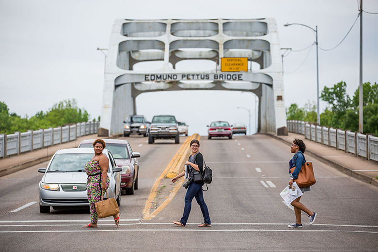Morgan State students Camille Harrison, left and Asha Glover, right, cross the Edmund Pettus Bridge with WVU student Colleen Good while reporting for the Bridging Selma project in Selma, Alabama.